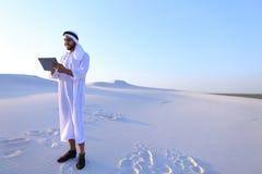 De succesvolle Arabische zakenman houdt in handen en gebruikt tablet, s Stock Afbeeldingen