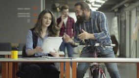 De succesvolle beambten delen het nieuws Gebaarde man op een fiets en mooie bedrijfsvrouw met documenten blij stock video
