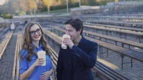 De succesvolle bedrijfsmens en de dame komen koffie samen bekijkend camera 4K stock footage
