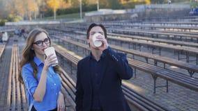 De succesvolle bedrijfsmens en de dame komen koffie samen bekijkend camera 4K stock video