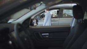 De succesvolle bedrijfsvrouw in een modieus kostuum die een nieuwe auto in een luxe kiezen auto toont Het autohandel drijven stock footage