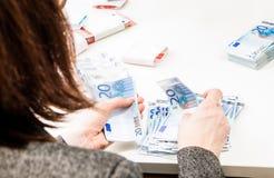 De succesvolle bedrijfsvrouw telt ona van geldrekeningen een bureau Stock Afbeeldingen