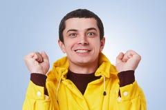 De succesvolle donkerbruine mens klemt vuisten met opwinding dicht, verheugt zich voltooiing of bereikend doelstellingen, heeft p stock foto's