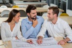 De succesvolle drie collega's werken aan plan van de bouw Stock Afbeeldingen