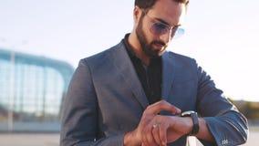 De succesvolle gebaarde mens in zonnebril regelt de tijd via slim horloge terwijl het lopen door de luchthaventerminal stock videobeelden