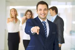 De succesvolle jonge bedrijfsmensen die duimen tonen ondertekenen omhoog terwijl status in meer interier bureau stock fotografie