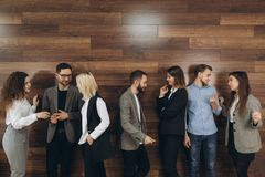 De succesvolle jonge bedrijfsmensen spreken en glimlachen tijdens de koffiepauze in bureau stock foto's