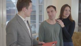 De succesvolle makelaar in onroerend goed vertelt over nieuw huis aan een jong leuk echtpaar Gelukkige man en vrouw die rond kijk stock videobeelden
