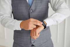 De succesvolle mens in een vest raakt zijn horloge stock foto