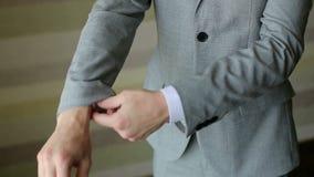 De succesvolle mens in het grijze kostuum maakt zijn kokers, close-up recht stock videobeelden