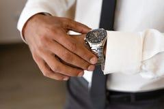 De succesvolle mens met witte overhemd en stropdas kijkt op horloge royalty-vrije stock afbeelding