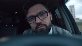 De succesvolle mens zit in de auto achter het wiel in een opstopping stock footage