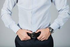 De succesvolle modieuze zakenman houdt zijn hand op riem Royalty-vrije Stock Afbeelding