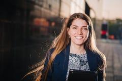 De succesvolle mooie jonge bedrijfsvrouw glimlacht op de achtergrond van gebouwen en houdt een tabletcomputer Royalty-vrije Stock Afbeeldingen
