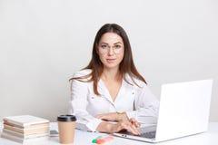 De succesvolle tekstschrijver bezig het werken met laptop computer, draagt om glazen, drinkt meeneemkoffie, stelt tegen witte bac royalty-vrije stock fotografie