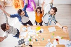 De succesvolle vier collega's drukken positieve emoties uit Royalty-vrije Stock Afbeelding