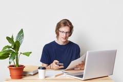 De succesvolle zakenman doet administratie, analyseert financiën, ontvangt berichten op slimme telefoon Jonge die mens met elektr royalty-vrije stock foto's