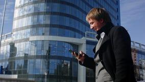 De succesvolle zakenman leest een bericht op zijn smartphone royalty-vrije stock foto's