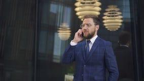 De succesvolle zakenman in ronde glazen wint baard die op telefoon spreken en bij zijn horloges met glasmuur letten op op stock video