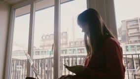 De succesvolle zekere jonge onderneemster glimlacht gebruikend laptop en smartphone bij hotelvenster in Parijs, trein die overgaa stock video