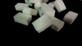 De suiker die pored op een stapel van suikerkubussen zijn Tegen zwarte achtergrond stock video