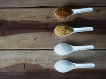 De suiker, het zout, de peper en het gefrituurde knoflook worden geplaatst op een witte lepel En de achtergrond is zwart Dit is v Royalty-vrije Stock Afbeeldingen