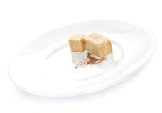 De suiker van de rietkubus en chocoladepoeder op een plaat op witte backgr Royalty-vrije Stock Afbeeldingen
