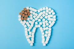 De suiker vernietigt het tandemail en leidt tot tandbederf Tand van wit en bederf wordt gemaakt van bruine suikerkubussen die wor stock foto