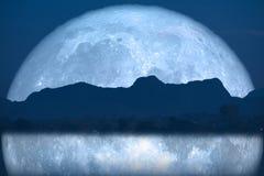 de super volledige achterbezinning van de vissenmaan over rivier en berg op nachthemel stock afbeelding