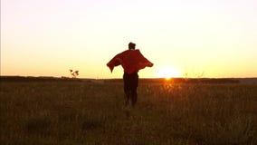 De superman in een rode regenjas vliegt in stralen van zonsondergang aan zijn droom en lacht Zakenman Hero comics stock videobeelden