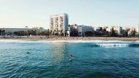 De surfer berijdt en zwemt op de raad die de golven van de oceaan ontleden voorraad Hoogste mening van een personenvervoer op een stock footage