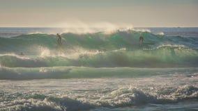 De surfers berijden een grote golf in winderige voorwaarden royalty-vrije stock fotografie