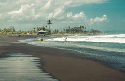 De surfers wachten golven op strand Stock Foto's