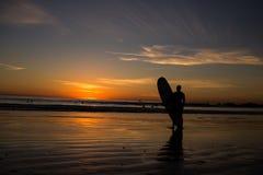 De surfplank van de surferholding bij strandzonsondergang Royalty-vrije Stock Foto's
