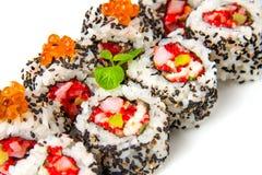 De sushi rollen met garnalen, vliegende vissenkuiten, zalm en zwarte sesam Royalty-vrije Stock Afbeelding
