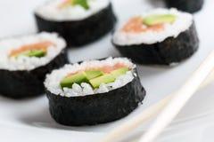 De sushi rolt met zalm, avocado, rijst in zeewier en eetstokjes op een plaat royalty-vrije stock foto's