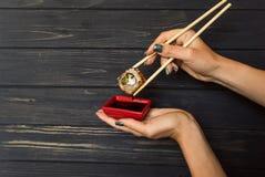 De sushi van de handholding met eetstokjes op een zwarte houten achtergrond stock foto