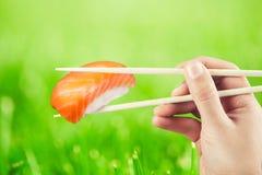 De sushibroodje die van de handholding eetstokjes gebruiken Royalty-vrije Stock Foto