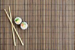 De sushibroodjes en de houten eetstokjes liggen op een serwing mat van het bamboestro Traditioneel Aziatisch voedsel Hoogste meni stock afbeeldingen