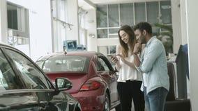 De Swarhtkerel en het mooie meisje gebruiken smartphone in autotoonzaal stock footage