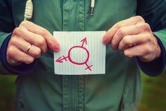 De symbolen van het geslacht Kaukasische witte volwassen mensenholding in handendocument met inschrijving op het transsexueelsymb Royalty-vrije Stock Afbeeldingen