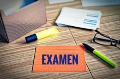 De systeemkaarten met wettelijke kwesties met glazen, pen en bamboe met het Duitse woord examen in Engels examen stock fotografie