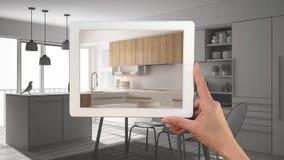 De tablet die van de handholding echte gebeëindigde minimalistische witte en houten keuken tonen Moderne keukencad schets of teke stock foto