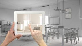 De tablet die van de handholding echte gebeëindigde moderne woonkamer met huiswerkplaats tonen Woonkamerschets of tekening op de  royalty-vrije stock foto