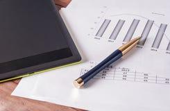 De tablet en de pen op de handelspapieren Stock Afbeeldingen