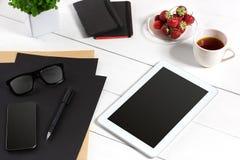 De tablet, het lege blad, de glazen en de koffie vormen op bureau houten lijst tot een kom Royalty-vrije Stock Foto's