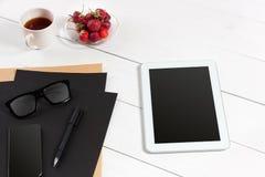 De tablet, het lege blad, de glazen en de koffie vormen op bureau houten lijst tot een kom Stock Foto's