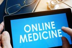 De tablet van de artsenholding met online geneeskunde stock foto