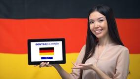 De tablet van de dameholding met leert Duitse app, de vlag van Duitsland op achtergrond, onderwijs stock footage