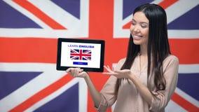 De tablet van de dameholding met leert Engelse app, de vlag van Groot-Brittannië op achtergrond stock videobeelden